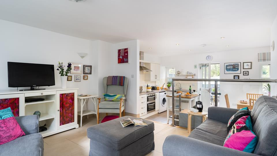 Bright open plan living space with door out onto rear patio area and parking.