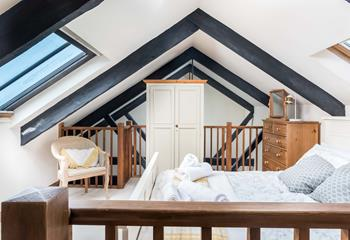Mezzanine level with double bed and light pouring in through Velux window.