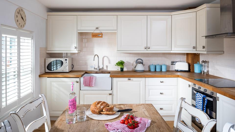 The modern kitchen has natural wood worktops and painted wood cupboards, bespoke shutters to the window maximise the light.