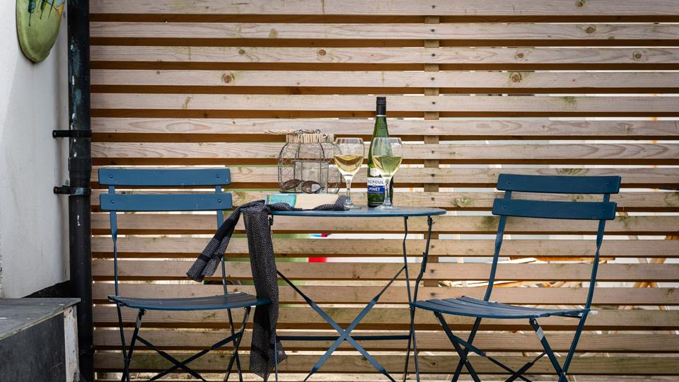 In the outside area, there is a painted metal bistro table and two chairs, just perfect for a glass of wine and a good book.