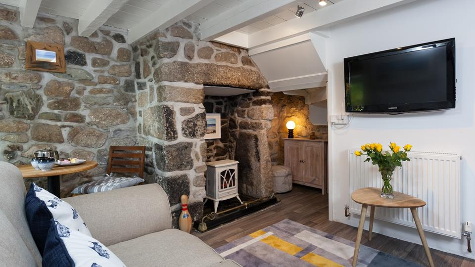In the sitting room area is a granite inglenook fireplace and accent wall with a cream enamel finish wood burner on a slate hearth.