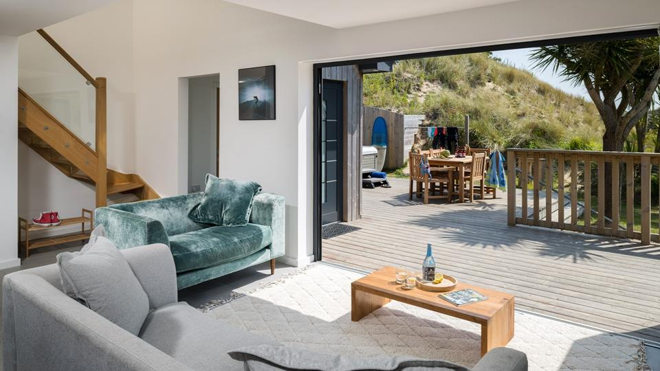 Bi-fold doors open up from the open plan living area onto the properties private decking area letting the Cornish sun pour in.