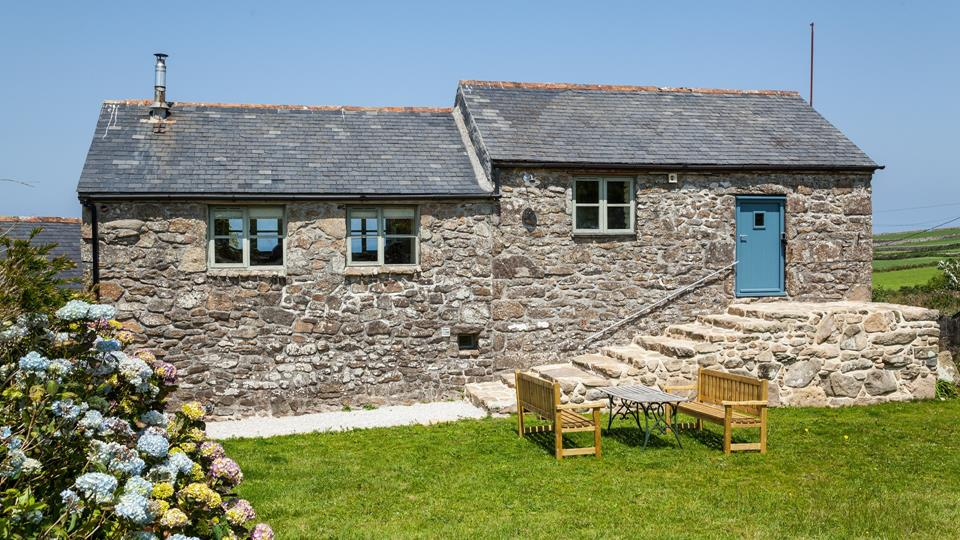 This reverse level farmhouse's entrance is situated at the back of the property up several shallow steps. The farmhouse also owns some outside furniture enabling you to enjoy your breakfast in the Cornish sun.