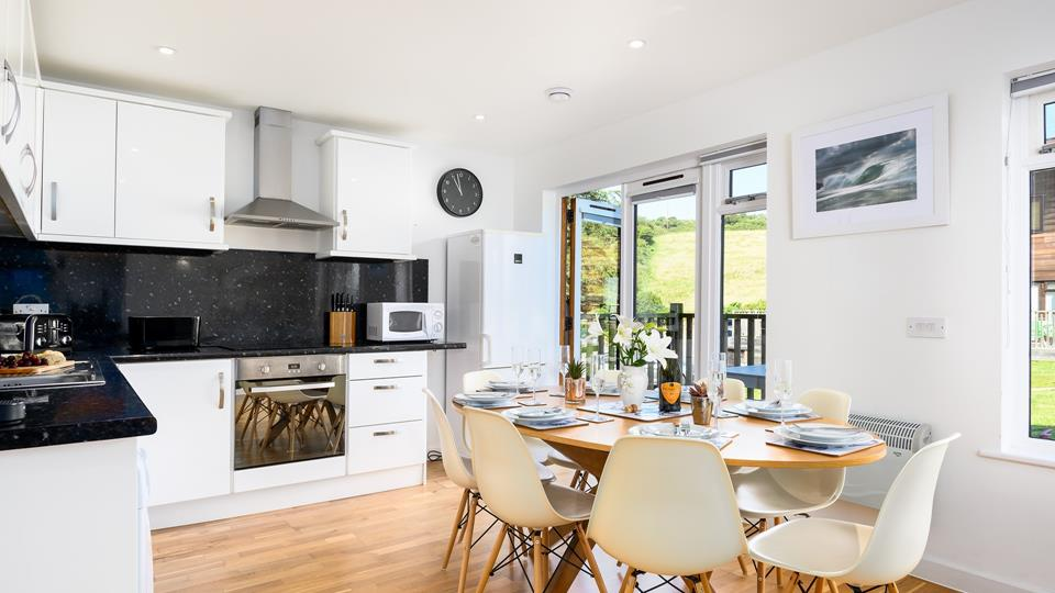 Dine in style in the open plan living space with doors out to the front decking area.
