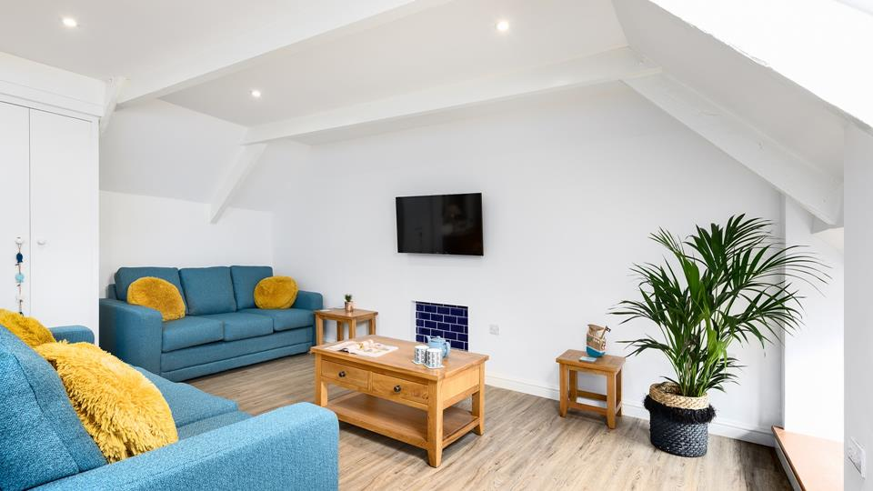 In the sitting area, there are two blue sofas with yellow accent cushions, a solid wood coffee table and a wall-mounted smart TV.