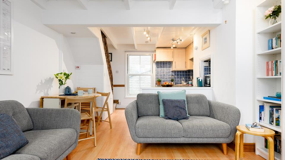 The living space has wood effect flooring throughout and painted exposed beamed ceiling.