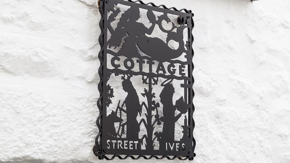 Bespoke metal art adorns the wall above the cottage entrance, beautifully and uniquely created.