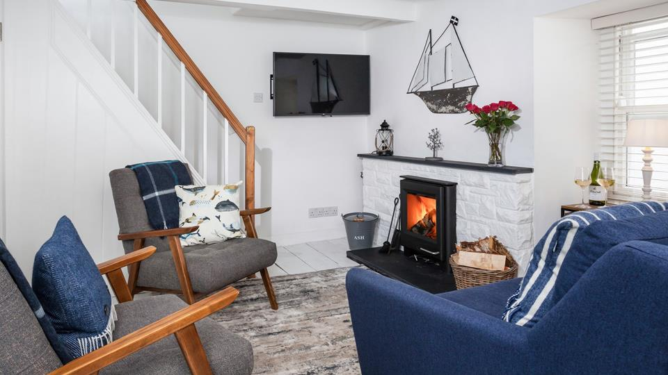 The living space has a wall-mounted Smart TV and has painted wood flooring with a cosy fireside rug.