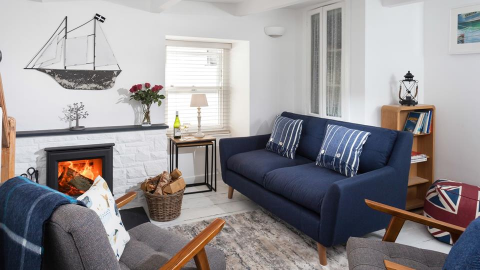 The sitting room area has a textile contemporary sofa, two armchairs and log-burning fire with slate hearth and mantle.