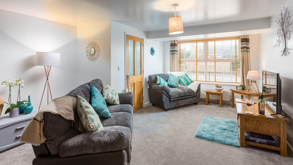 Lovely spacious sitting area with two lovely new sofas and tastefully chosen solid wood furniture with some great interior design touches.