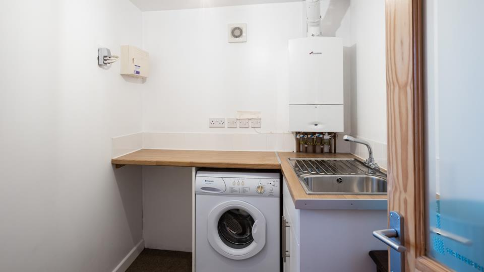 The utility area has a sink with drainer, plenty of worktops and a washing machine.