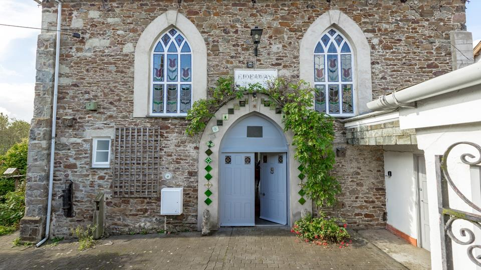 Hideaway House has a fantastic entrance with original stained glass windows and a beautiful wisteria climbing around the arched entrance doorway.