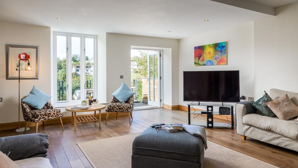 The stylish living area encompasses solid oak flooring, patio doors, sumptuous sofas, leopard print chairs, contemporary artwork and minimalistic lighting.
