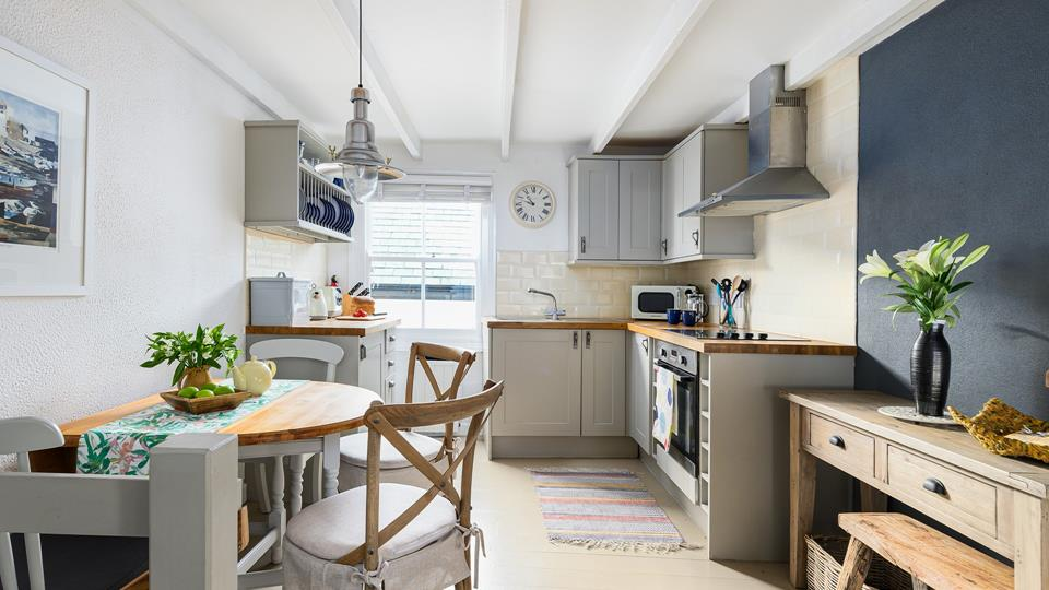 Chic and sophisticated, warm greys and wooden furniture add a country feel to the kitchen.
