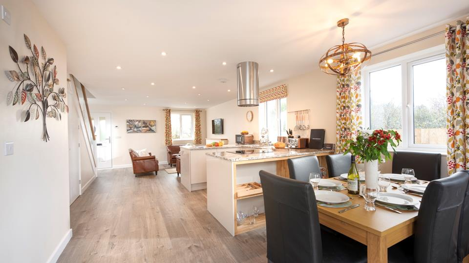 Spacious open plan living area with stairs rising to first-floor en suite bedrooms.
