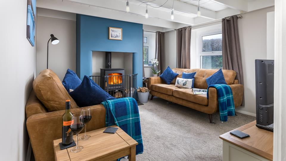 The sitting room has two leather contemporary style sofas and a simplistic and minimalistic lighting feature.