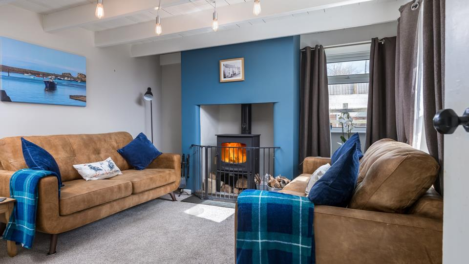 The sitting room has painted exposed beams and original fireplace with a wood burner to cosy up in the evenings.