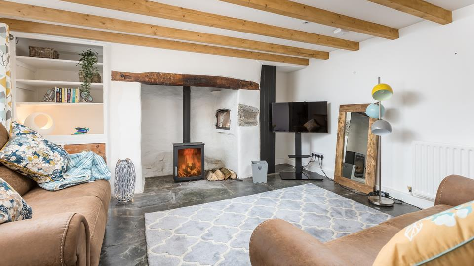 The sitting room has the original inglenook fireplace with a wood burner and a clome oven feature, the ceiling has exposed beams and a local Delabole slate flagstone floor.