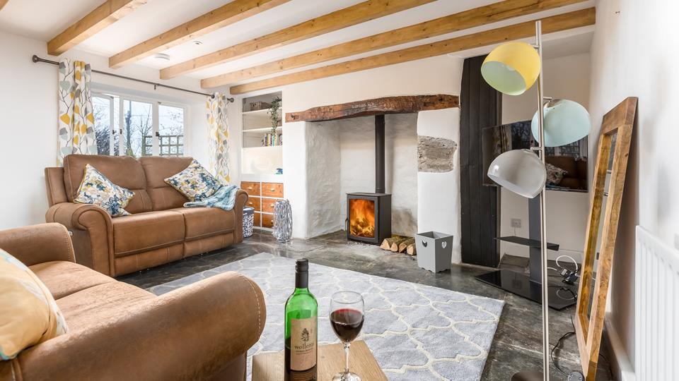 The sitting room has two leather electric reclining sofas for ultimate comfort whilst enjoying the cosy wood burner.