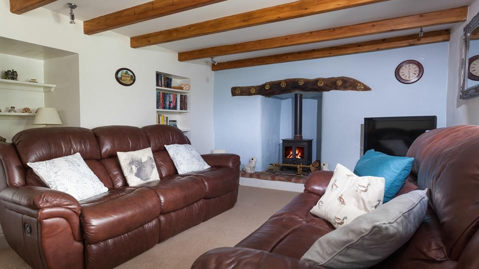 The second living area with its classic leather sofas and cosy woodburner is a great space to snuggle up.