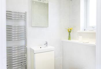 The bathroom is a bright and uncluttered space with sleek and practical furnishings.