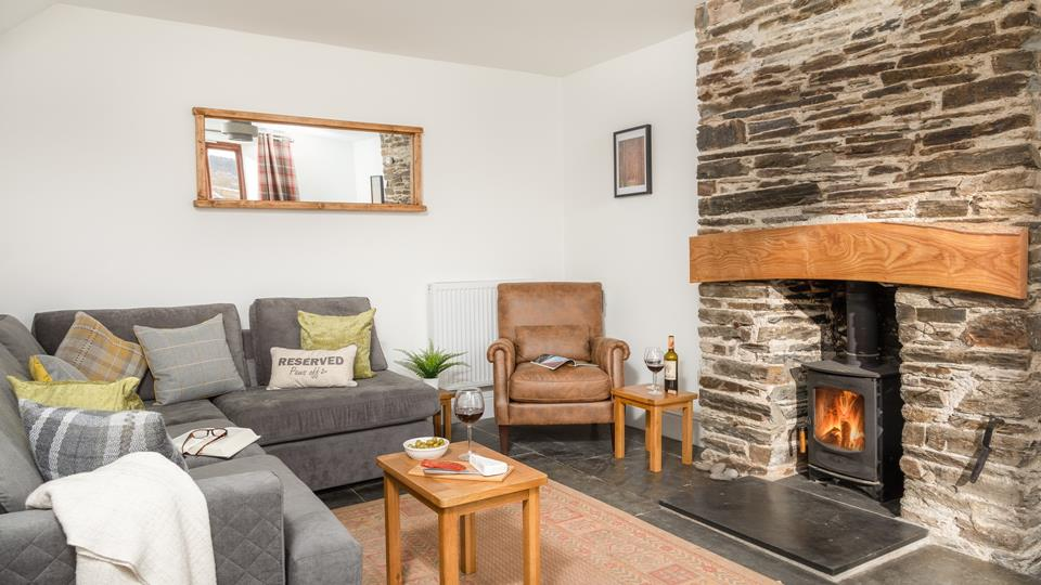 The lounge complete with plush furnishings in muted tones and a woodburner offers a cosy country vibe.
