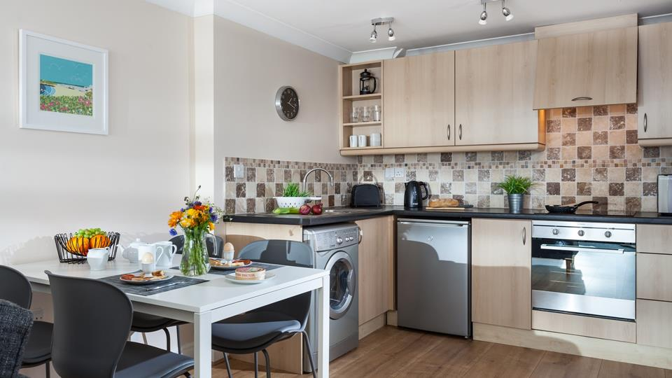 The kitchen has a cute country vibe and is fully equipped with modern appliances to make cooking delicious meals a breeze.