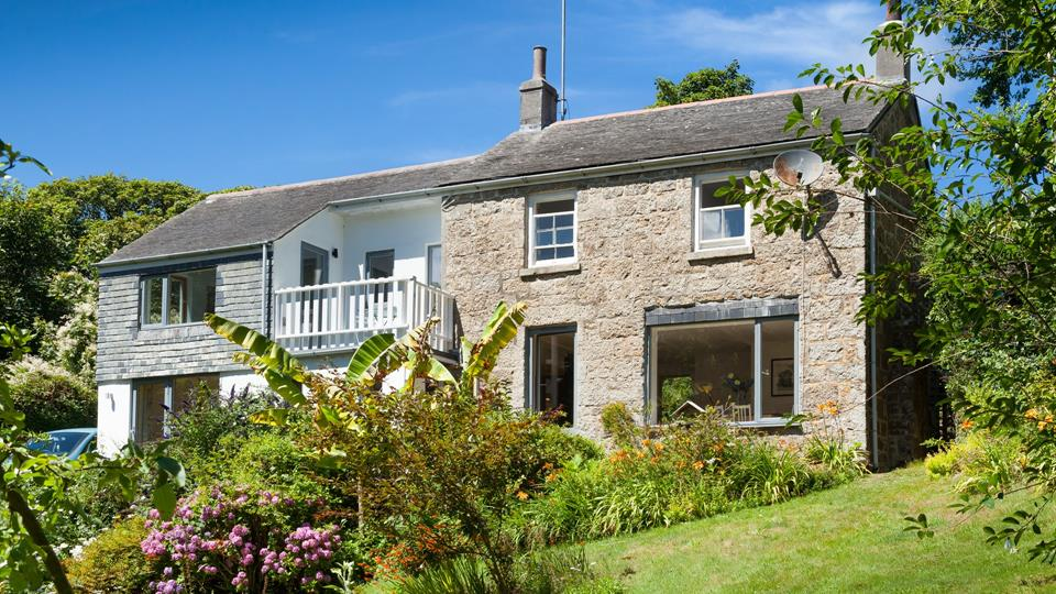 Treverven Cottage with large windows and balcony to enjoy the beautiful garden views.