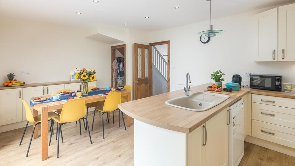 The kitchen and dining area has wooden effect flooring and has a well-equipped kitchen including a dishwasher and microwave.