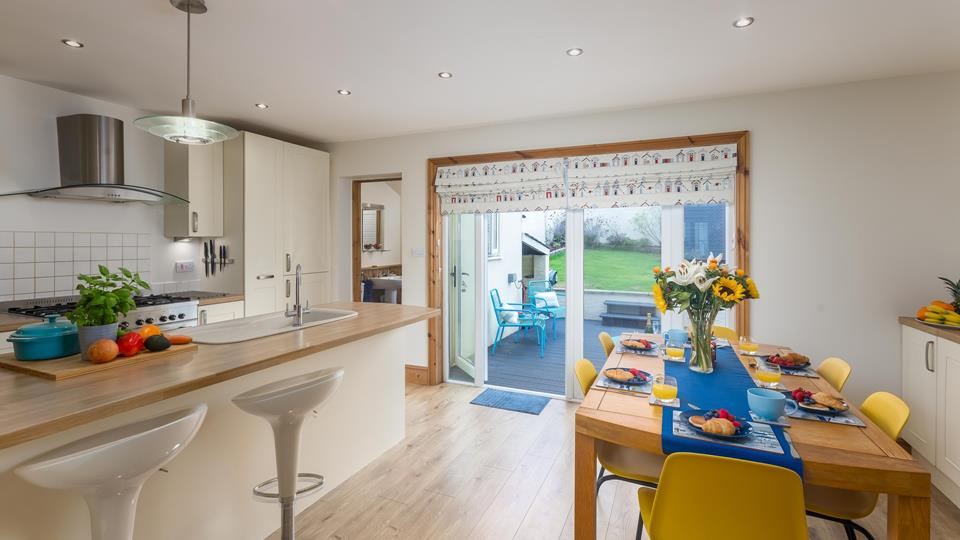 The kitchen and dining area has a breakfast bar with two swivel stools and patio doors lead out onto the decking and garden area.