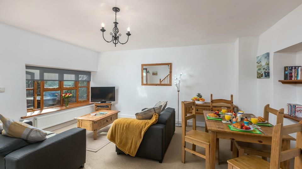 The spacious open plan living space has two comfy textile sofas and natural solid pine wood table and chairs.