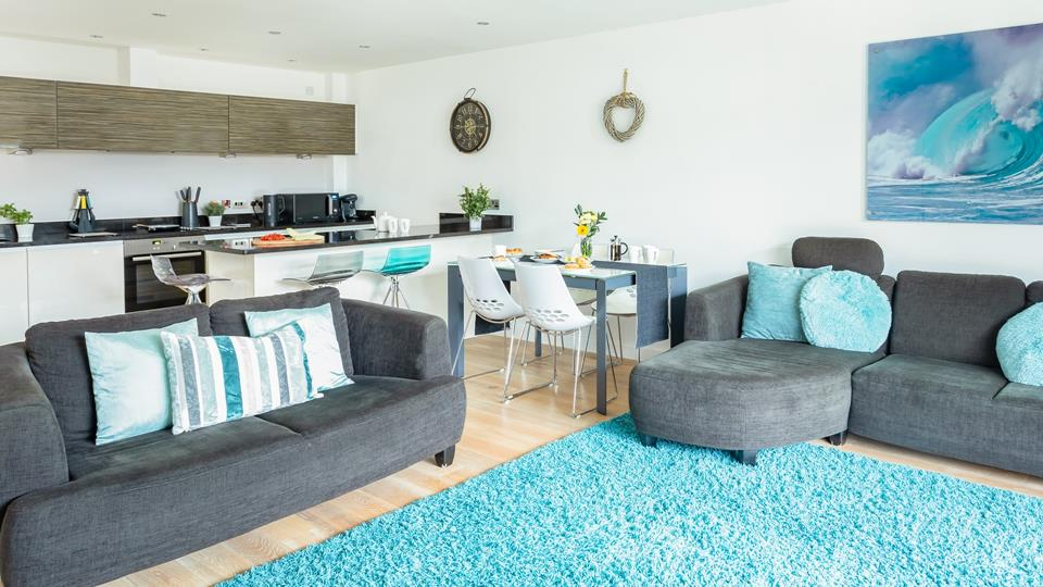 The lovely open plan living area is complemented by the colours of the surrounding coast.