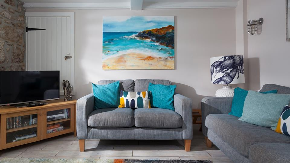Beautifully finished with bold blues and striking coastal artwork, the sitting room echoes Trelither's seaside location.