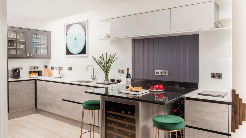 The kitchen blends a cool, modern colour palette with luxurious, rich fabrics, creating a stunning space to cook and eat.