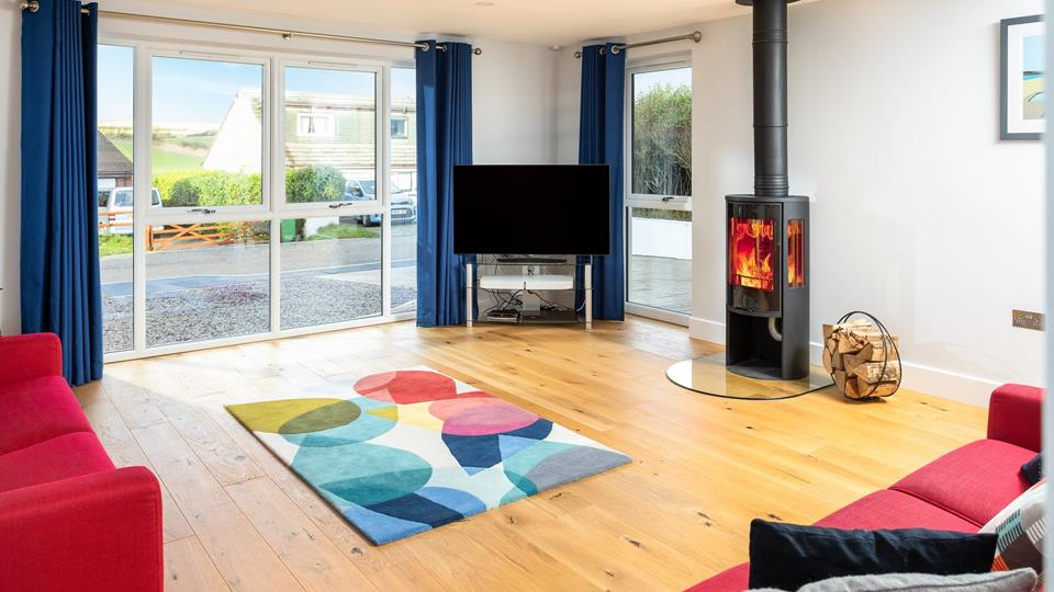 The sitting room has a woodburner, wooden flooring and dual aspect windows providing a great sociable and light living space.