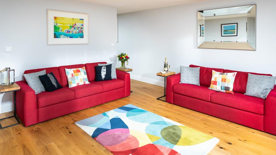 Vibrant textile sofas and an abstract rug with coordinating accent cushions and artwork have created a fantastic vibe in the living area.