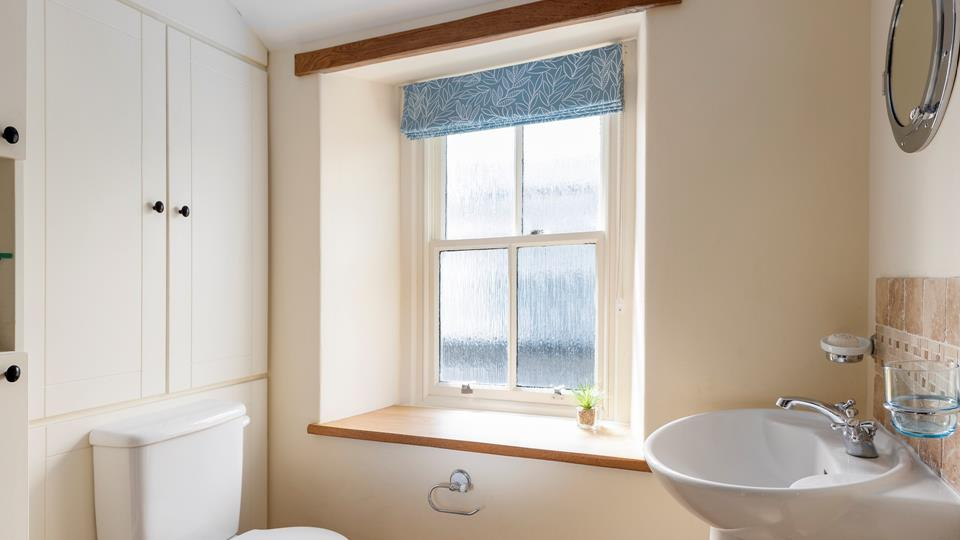The character of the cottage continues into the family shower room, with an exposed beam and a deep window sill.