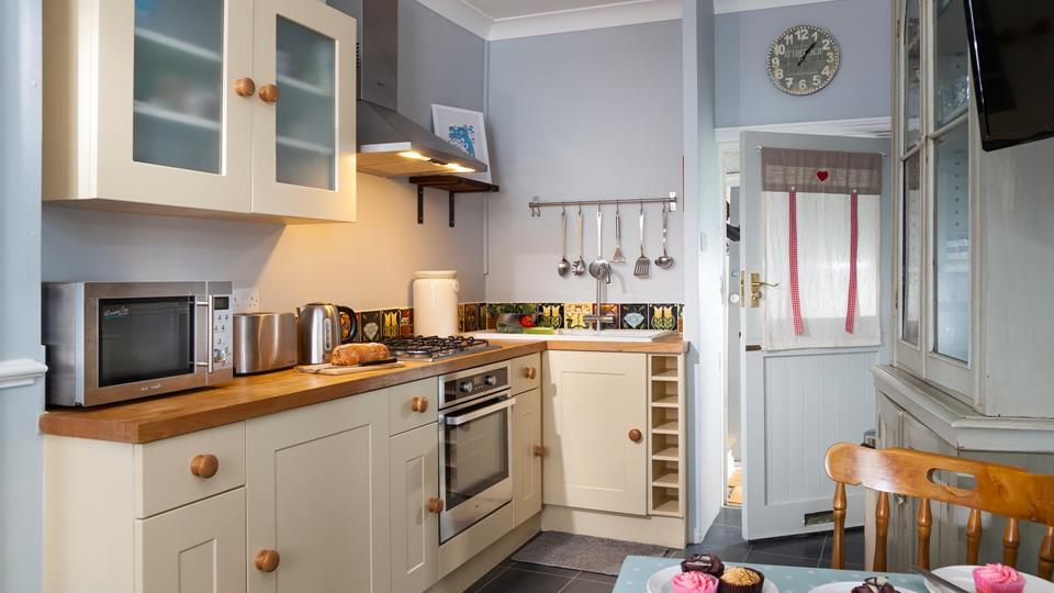 Finished in cream and pastel blues, with slate flooring, the kitchen has a countryside vibe.