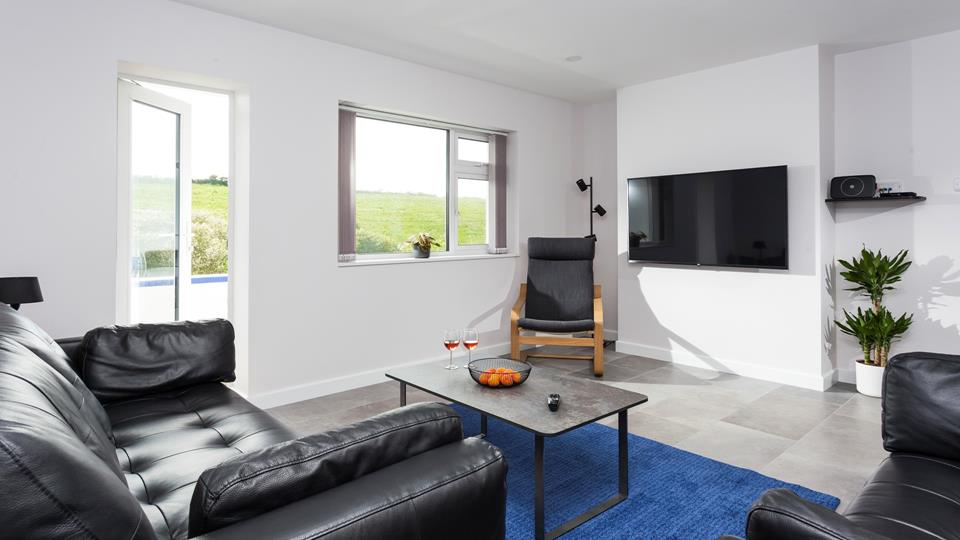 Bright and airy, the open plan sitting room features a door leading to the balcony.