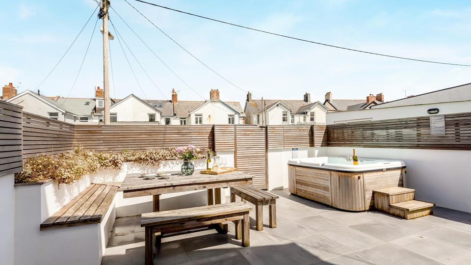 The outside area is a designer garden with bespoke L-shaped seating and a solid natural wood table and bench seating, and the hot tub is the perfect relaxation zone.