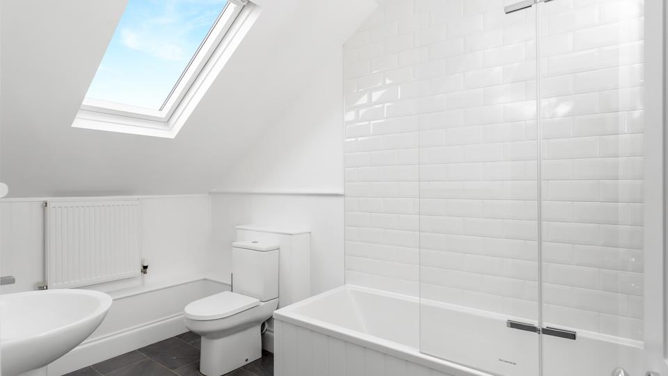 The family bathroom on the second floor has a bath with shower above and a large Velux window which provides plenty of light.