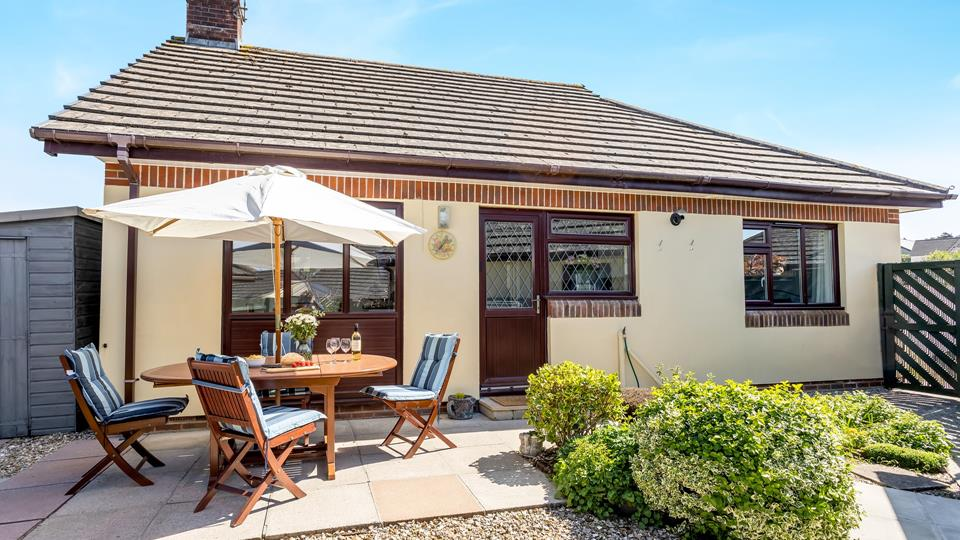 Private and enclosed outside area with teak outside table, chairs cushions and parasol.