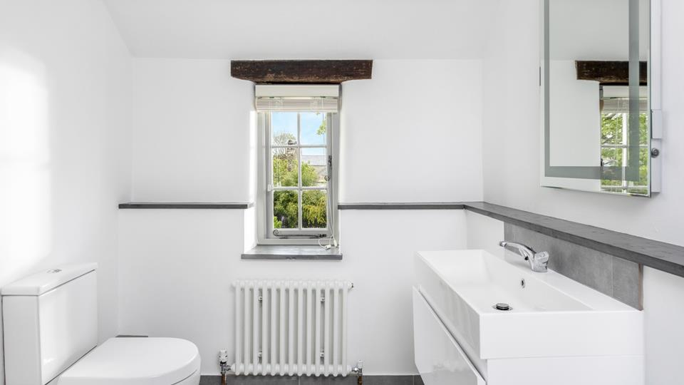 The family bathroom has a window overlooking the shared garden, an illuminated mirror above the basin with a continual natural slate shelf which is so useful for bathroom products.