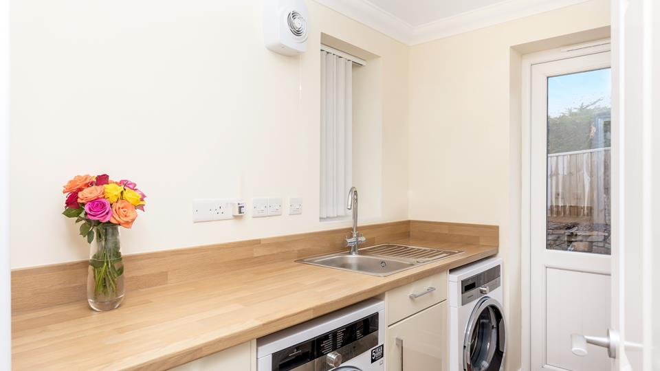 The utility room has a washing machine and separate tumble dryer, there is a glazed door leading out to the side of the property all with level access.