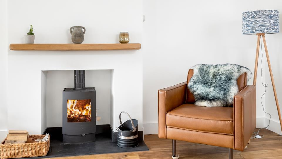 The wood burner in the sitting room area has a solid oak mantle with natural Delabole slate hearth and the leather armchair adjacent with the tripod standard lamp and bespoke lampshade looks great.