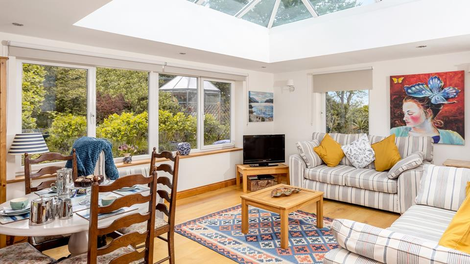 Light and space are achieved by the conservatory raised roof in the living space.