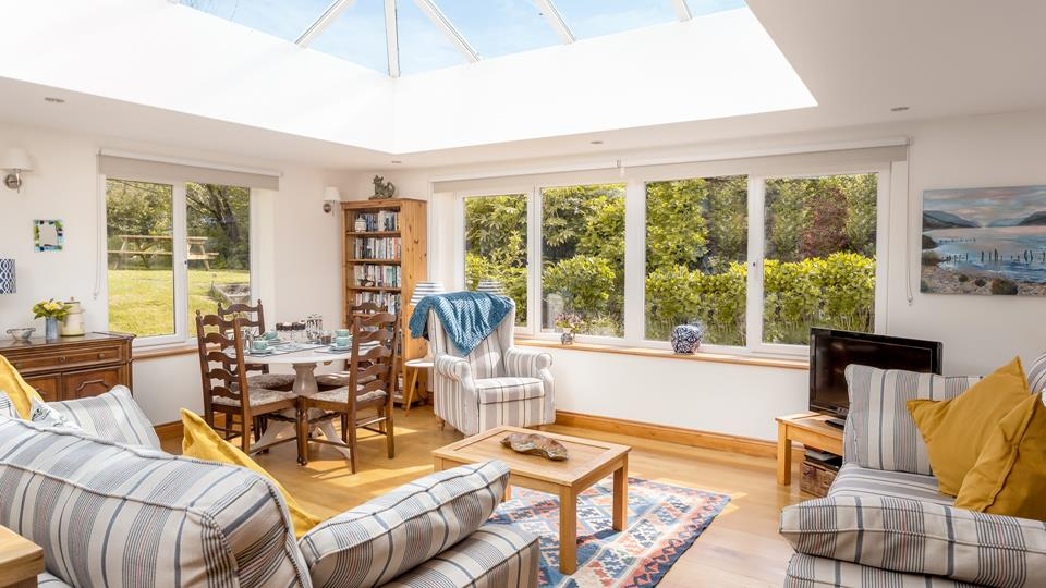 The living space is a sunny room and has two large comfy textile sofas with natural wood effect flooring and triple aspect windows, overlooking the garden area with a raised sunroom conservatory providing oodles of light.