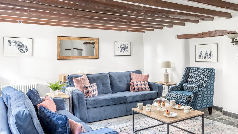 The sitting room has exposed beams which compliment the original exposed lintels, there are two textile sofas and a high back armchair for ultimate comfort.
