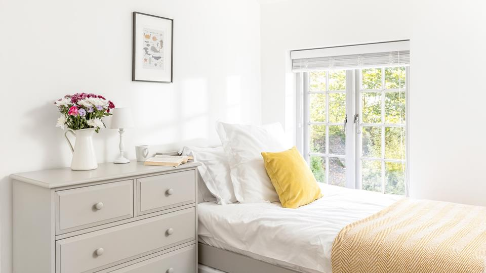 Bedroom three has twin single beds and there is a painted wood chest of drawers to the side for really handy storage. This bedroom overlooks the rear shared grounds.