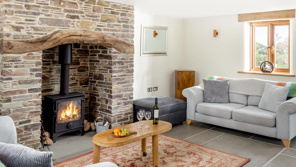 The sitting area has a natural stone inglenook fireplace with a reclaimed solid wood lintel above and local slate hearth, just perfect to enjoy the woodburner.